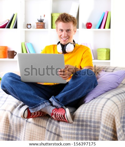 Young man relaxing on sofa with  laptop - stock photo