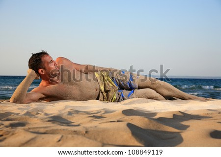 young man relaxing on the beach enjoying the sea