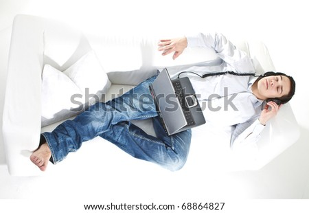 Young man relaxing on the couch listening to music over white background. - stock photo