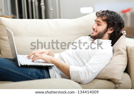 Young man relaxing on the sofa with a laptop - stock photo