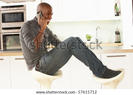 Young Man Relaxing Sitting In Kitchen Talking On Phone