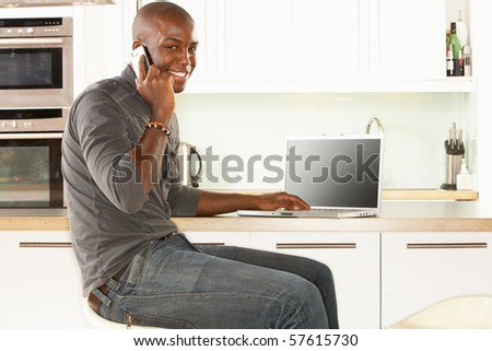 Young Man Relaxing Sitting In Kitchen Talking On Phone - stock photo