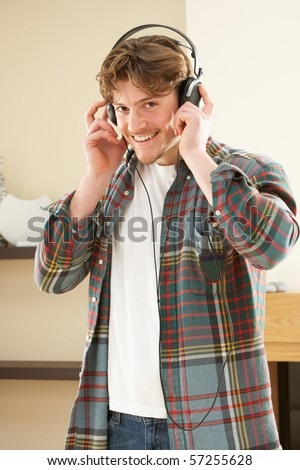 Young Man Relaxing Sitting On Sofa Listening to Music At Home On Headphones - stock photo