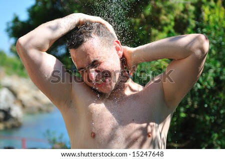 young man relaxing under shower