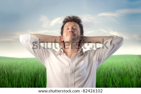 Young man relaxing with green meadow in the background - stock photo