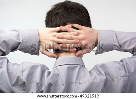 Young man relaxing with his arms crossed behind head - stock photo