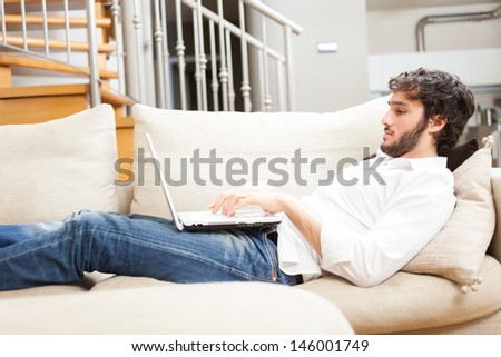 Young man relaxing with his laptop on the sofa - stock photo