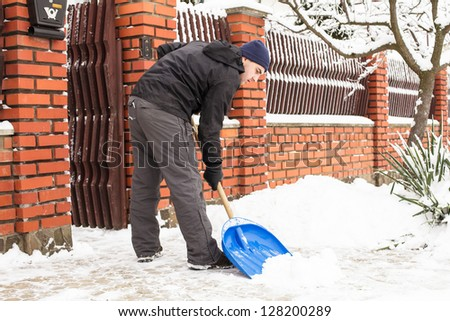 Young man remove snow near the suburban house - stock photo