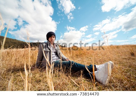 Young man rest on golden field. - stock photo