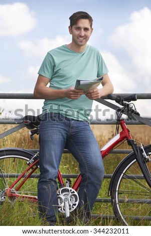 Young Man Resting On Gate And Looking At Map On Cycle Ride