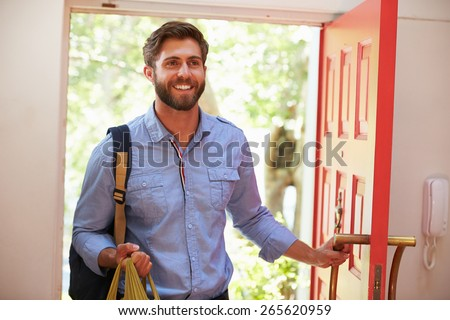 Young Man Returning Home For Work With Shopping - stock photo