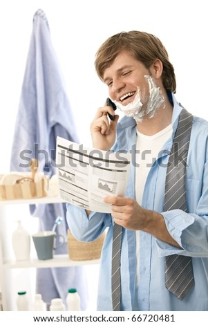 Young man reviewing document and talking on mobile while shaving in the morning. Isolated on white? - stock photo