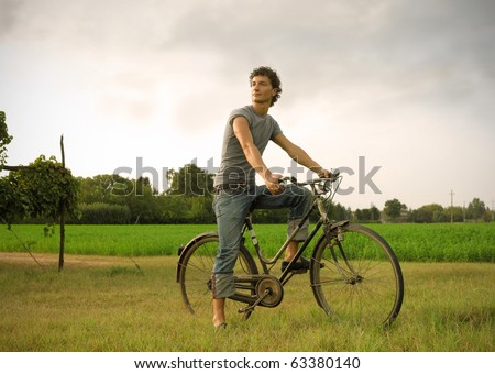 Young man riding a bike in a field