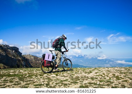 Young man riding a bike over the precipice in the mountains - stock photo