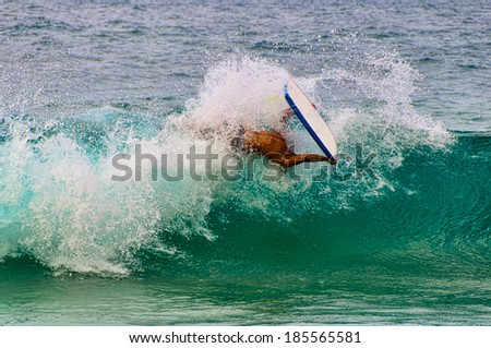 Young man riding a boogie board in a blue wave in the summer. - stock photo