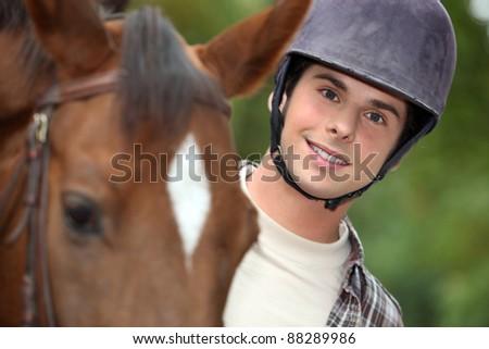 young man riding a horse - stock photo
