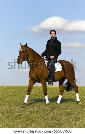 Young man riding a horse in the fields by the countryside - stock photo