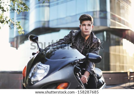 Young man riding a motorbike View of a man with a motorcycle on the background of the cityscape - stock photo