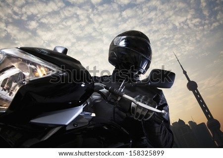 Young man riding a motorcycle during the day - stock photo