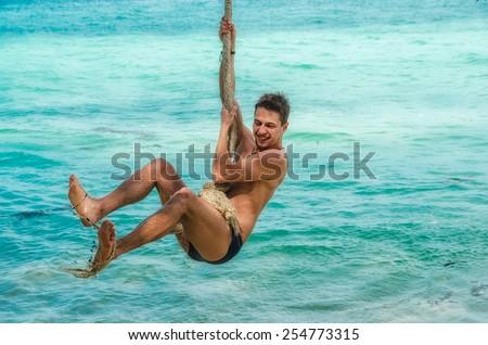 young man riding a tarzan rope at the tropical sea - stock photo