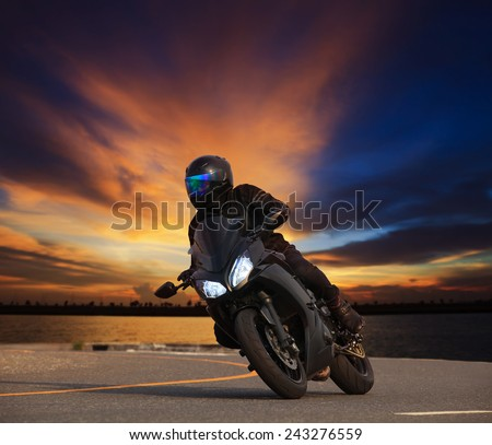 young man riding big bike motorcycle leaning curve on asphalt highways road against beautiful dusky sky use as people adventure sport leisure theme - stock photo