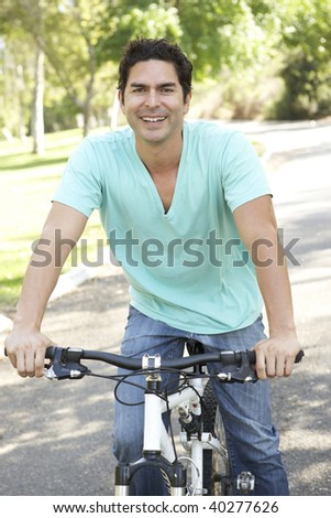 Young Man Riding Bike In Park - stock photo