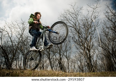 Young man riding bike, low angle view, motion blur - stock photo