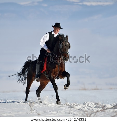 young man riding horse outdoor in winter - stock photo