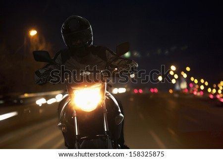 Young Man riding motorcycle at night - stock photo