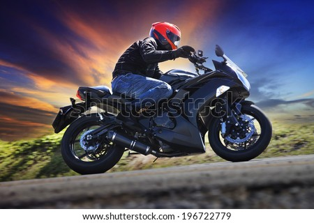 young man riding motorcycle on curve of asphalt country road against dusky sky use for sport activities,male leisure and journey theme - stock photo