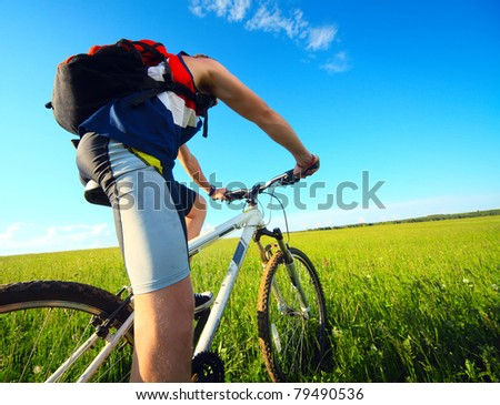 Young man riding on a bicycle on green meadow with a red backpack - stock photo