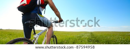 Young man riding on bicycle on a green meadow with red backpack - stock photo