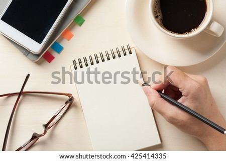 Young man right hand writing on blank notebook on wood table with coffee cup, smartphone, and glasses beside in morning time - stock photo