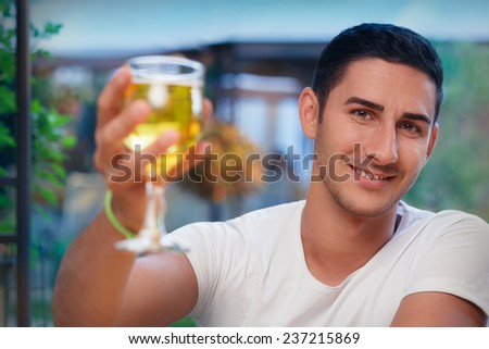 Young Man Rising a Glass in a Bar- Portrait of a handsome man drinking and making a toast  in a restaurant pub   - stock photo