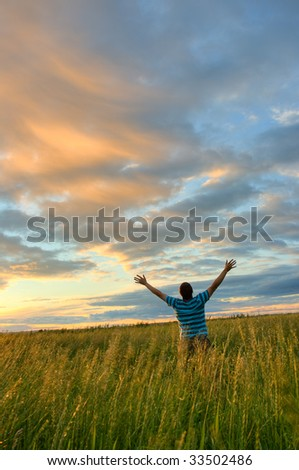young man rising hands over sunset