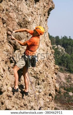 Young man rock climbing on a limestone wall. - stock photo