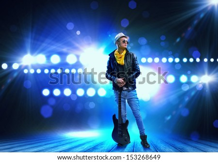Young man, rock musician in jacket with guitar