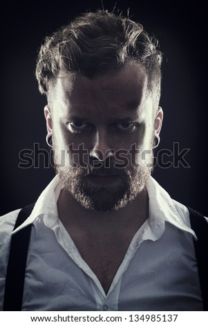 Young man / rocker with ear rings. Smoke and scene light.