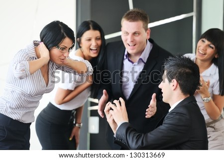Young man romantically proposing to girlfriend offering engagement ring at working place in front of friends and colleagues - stock photo