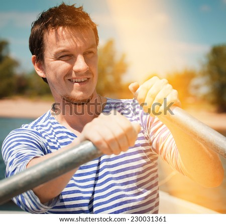 young man rows the boat (filtered) - stock photo