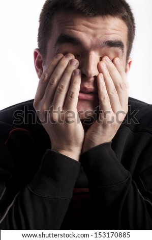 Young man rubbing his eyes