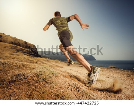Young man runner running on a dusty country road. Jogger training workout in fitness shoe. Healthy lifestyle and sport concept.
