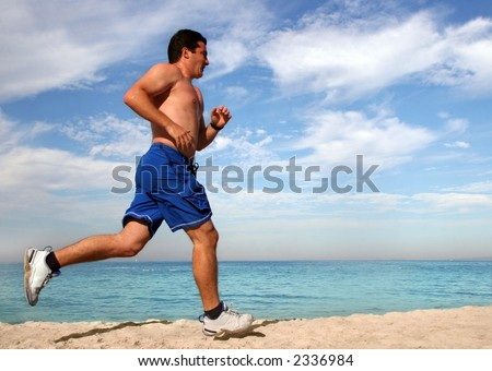Young man running alone on the beach - stock photo