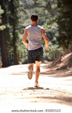 Young man running along country lane - stock photo