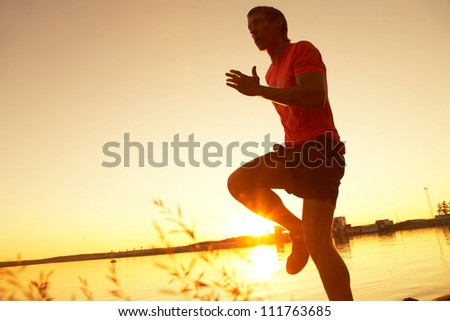 Young man running along the seashore at sunset - stock photo