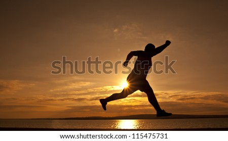 Young man running along the seashore at sunset