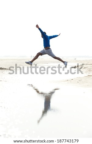 Young man running and jumping at the beach. Athletic male in sportswear outdoors  - stock photo