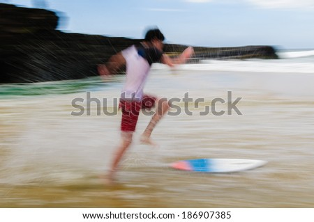 Young man running and jumping on a skim board in shallow water on a sandy beach in Maui, Hawaii, USA - stock photo