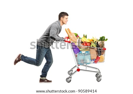 Young man running and pushing a shopping cart full with food isolated on white background - stock photo