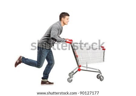 Young man running and pushing an empty shopping cart isolated on white background - stock photo